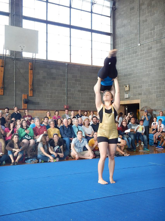 One performer holds another above her head, forming a T.