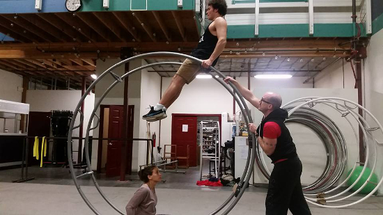 An aerialist practicing on a giant wheel with two helpers assisting