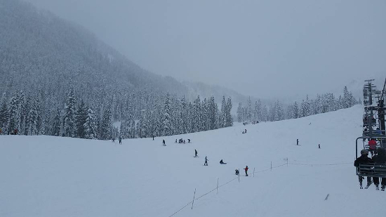 A snowy ski mountain with skiers descending the mountain