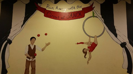"A painting of a man juggling and a woman hanging from a ring. Above is the caption: ""run away with the circus at SANCA"""