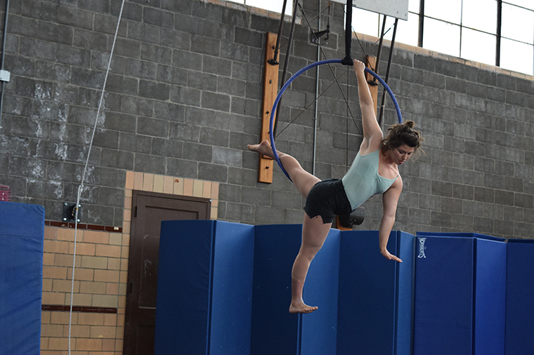 A student hangs onto a gymnastics ring in the air