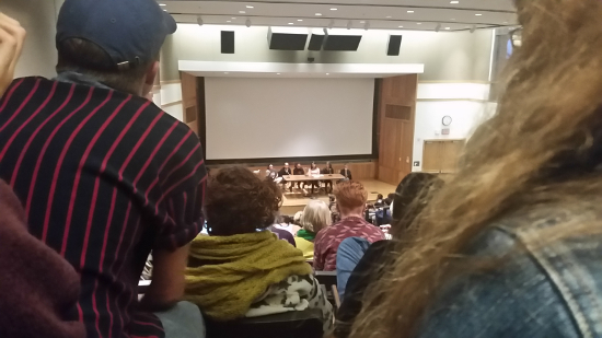 A back row view of a full audience of people sitting in dye lecture hall. On the stage is a table with 6 professor sitting
