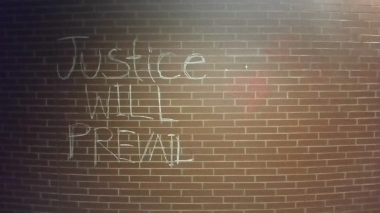 "A brick wall with the words ""justice will prevail"" chalked on the wall"