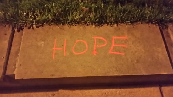 "The word ""hope"" chalked on a stone in the sidewalk"