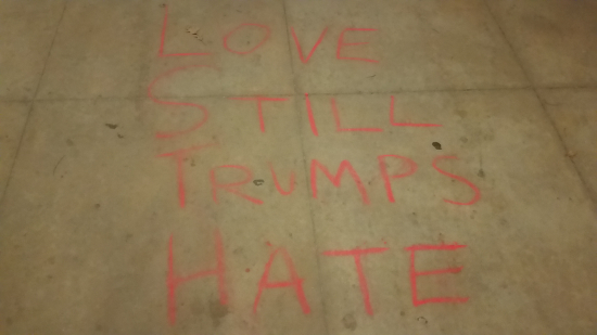 """love still trumps hate"" chalked on the sidewalk"