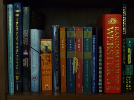 Books including a dictionary, several Tolkien books, The Ultimate Encyclopedia of fantasy, a Star Trek guide, and a couple of Terry Pratchett books.