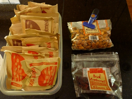 Lots of oatmeal packets, a bag of almonds, and a package of dried cranberries.