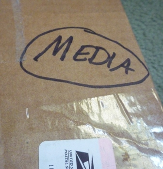 A box is taped up for shipping, with the word Media handwritten with a marker