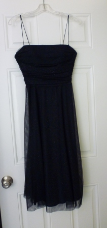A shoulder-less black dress on a hanger