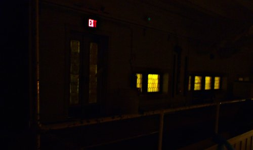 A dark photo showing the light of an exist sign and the yellow of windows