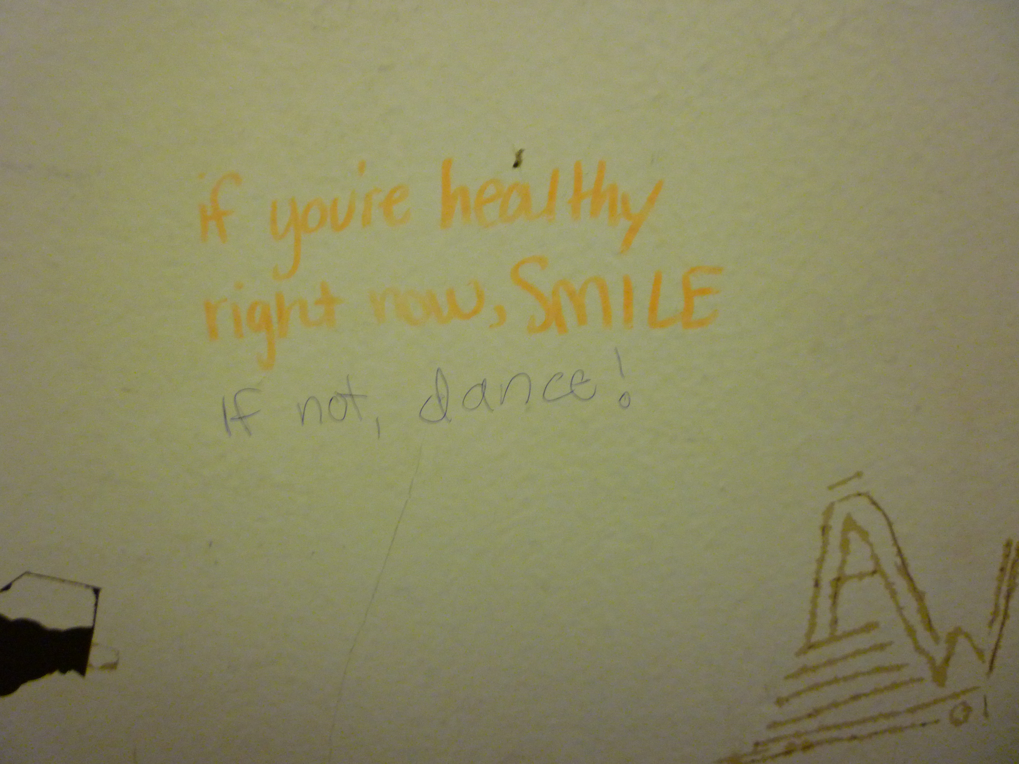 "Graffiti written on a stall that says ""if you're healthy right now, smile. If not, dance"""