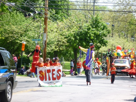 The SITES kids walk in the parade next to circus performers.