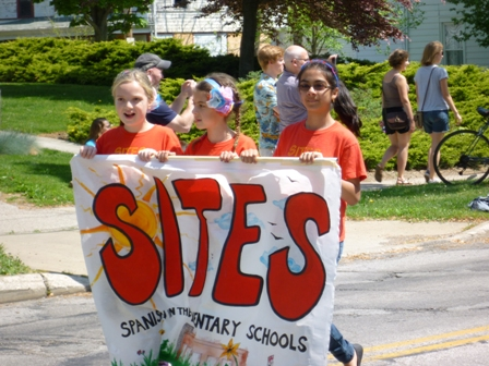 3 kids carry a banner: SITES Spanish in the Elementary Schools