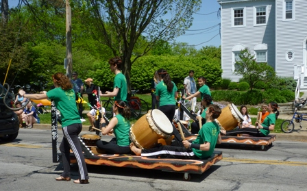 Taiko drummers on wheels hold their sticks ready.