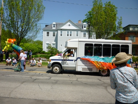 A couple of people carry a colorful dragon's head, followed by a small bus with matching colors on it.