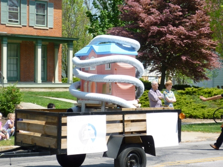 A dollhouse with a tube wrapped around it sits on a trailer.