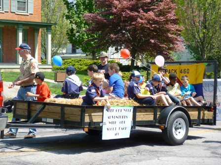 Boy scouts riding on a hay-covered trailer.