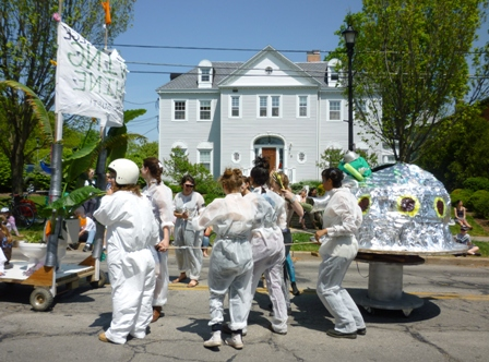 People in white jumpsuits and a metallic-looking object