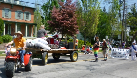 A wagon pulls a drummer playing a full drum kit, along with amplifiers, followed by marching electric guitarists.