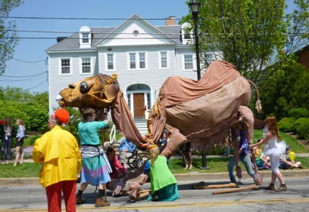 Several people move the elaborately-constructed camel.