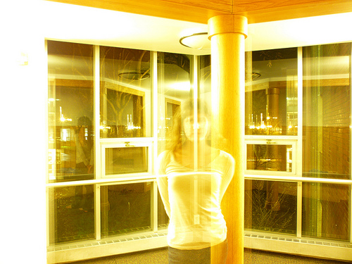 A transparent body stands in a yellow room