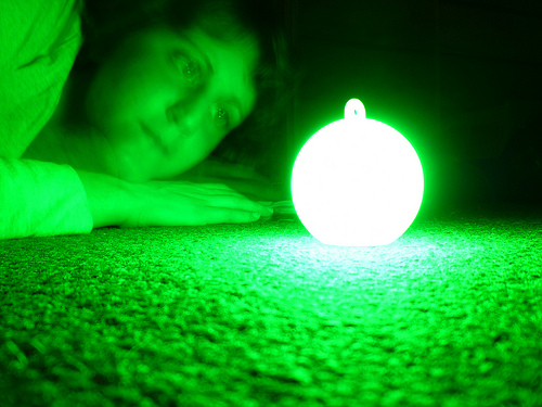 A student lays next to a glowing green orb