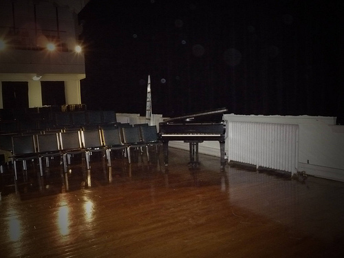 Piano and empty chairs in a recital room