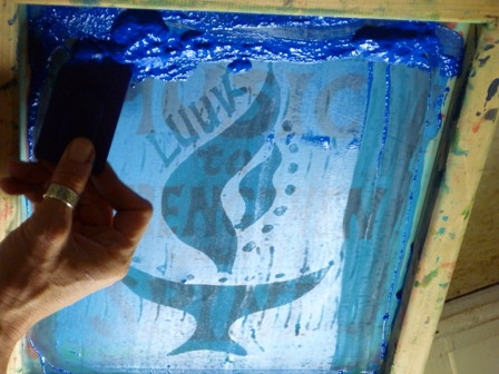 Hands spreading paint on a screenprinting template