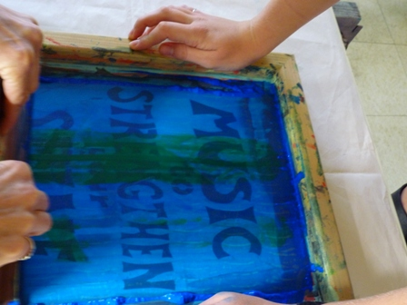 hands spread paint on a template