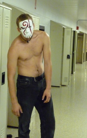 A shirtless student with a mask on