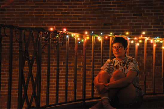 Student sits in front of a railing with string lights