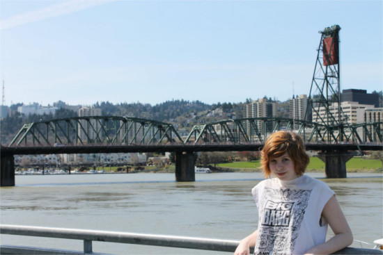 Student posing in front of the Portland riverfront