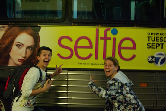 "Two people point to an advertisement with the word ""selfie"""