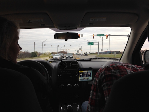 A view from the backseat of the car. In the front sits the authors mom and brother. They are driving on highway