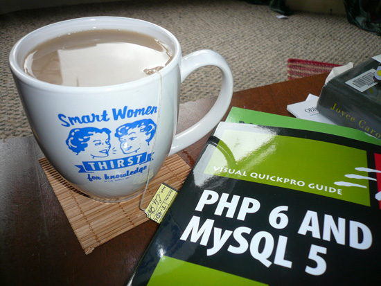 "A book titled ""Visual Quickpro Guide: PHP 6 and MySQL 5."" Next to it sits a mug of tea with the words ""smart women thirst for knowledge"""