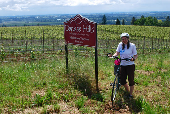 "The author standing with her bike in front of a valley and a sign that says ""Dundee Hills"""