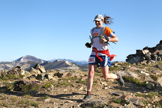 The author running in front of a scenic view of rocks and mountains