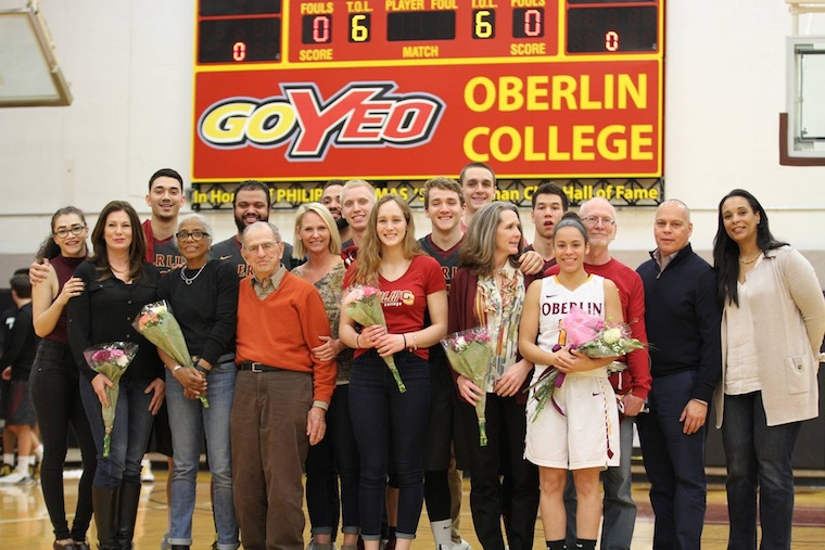 Student athletes pose for a picture holding flowers with their parents on the basketball court