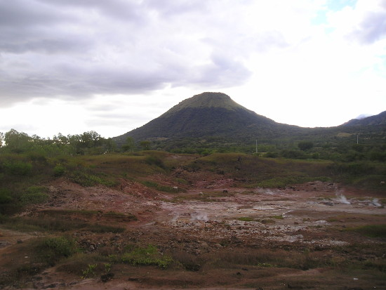 A view of a volcano from afar and on the ground. The ground is dry with patches of green