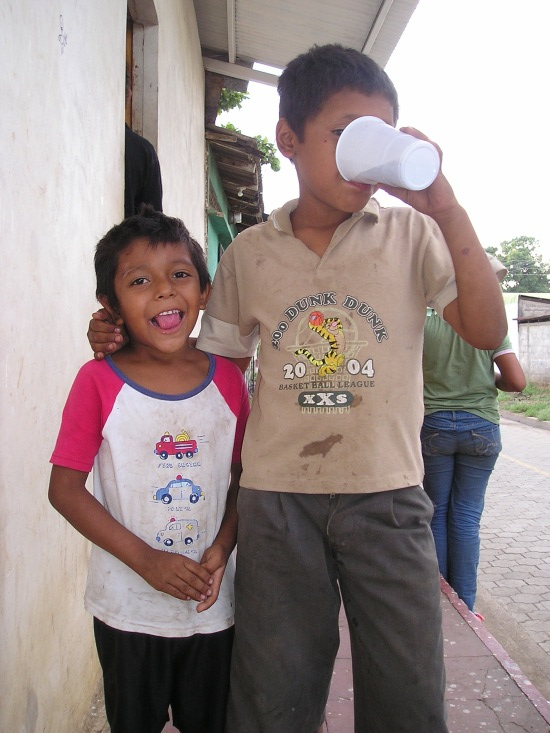 Two young boys posing. One is much taller and is drinking from a cup with his arm over the others shoulder. The other boy is smiling for the photo.