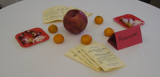 "A table with a ""reserved"" tab, oranges, and a lantern"