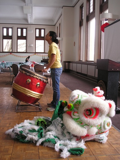 A student drumming, a dragon costume sits next to them