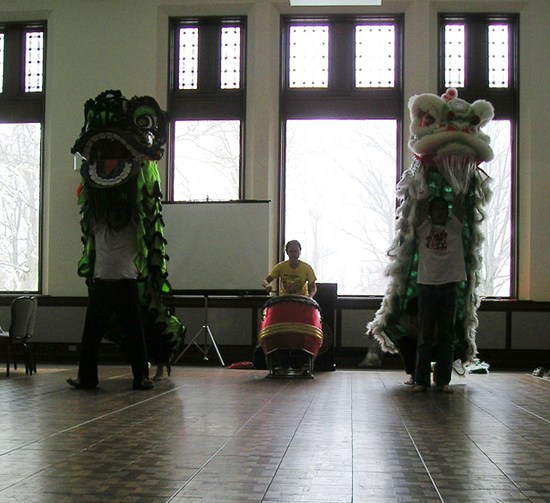 The drummer in the middle of two people wearing dragon costumes