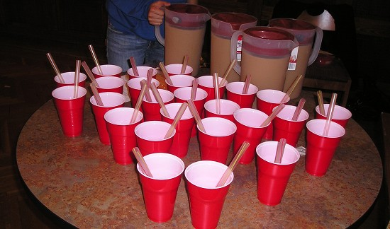 Many red cups with wide straws, and 4 pitchers of tea.