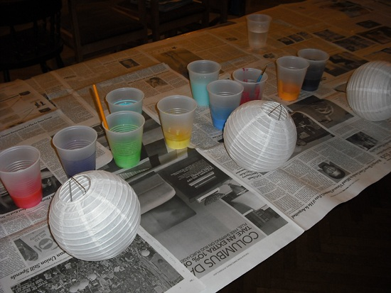 Unpainted lanterns on newspaper next to cups of colorful paint.