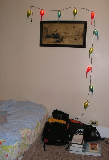 The foot of the bed with bags and lights on the wall