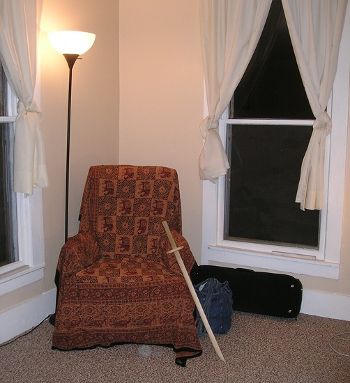 A rocking chair in a corner with a wooden sword propped against it