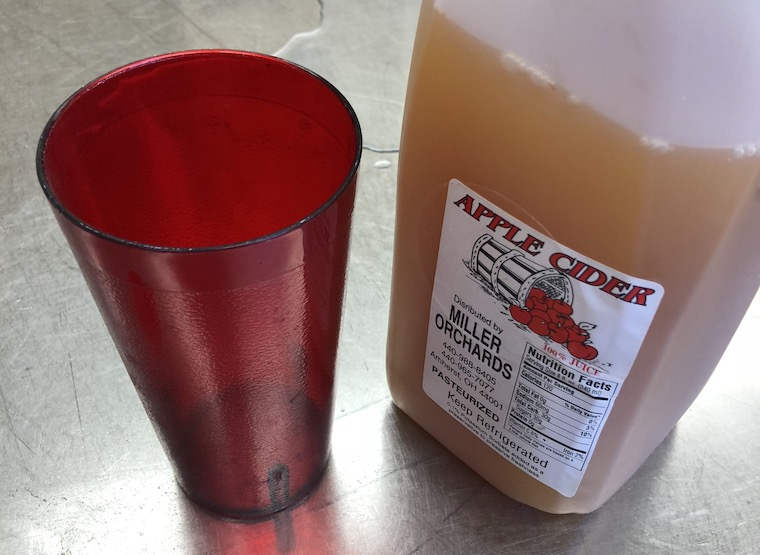 A red cup next to a jug of apple cider