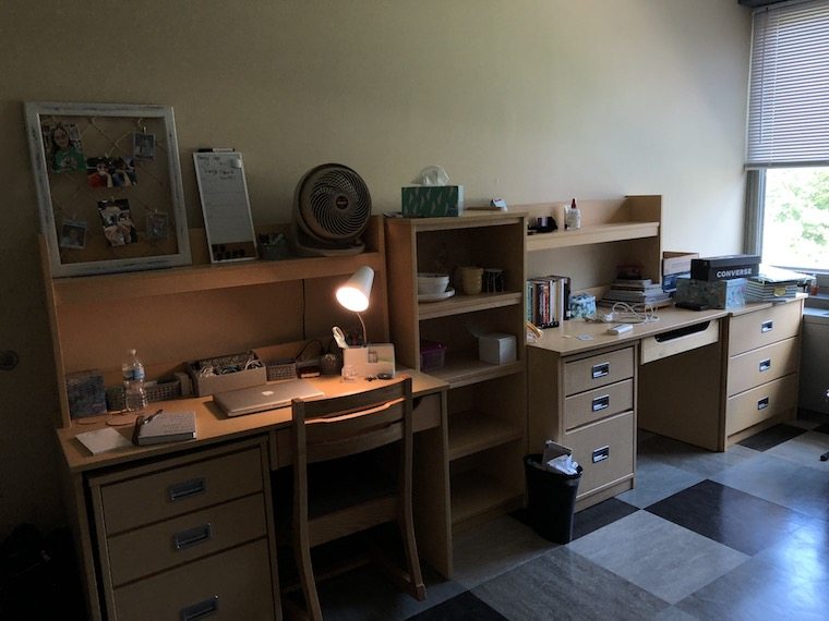 Two dorm room desks, side by side, with a bookshelf in the middle. Various office items are scattered atop the desks.