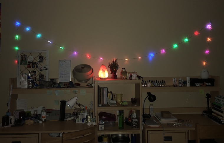 Two desks, side by side, decorated with many trinkets, and a bookshelf, also very decorated, between them. A string of colorful lights hangs above the desks, and a salt lamp shines on top of the bookshelf.